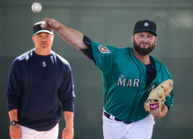 Pitcher Ryan Cook throws in the bullpen in spring training with bullpen coach Mike Hampton watching.   (Bettina Hansen / The Seattle Times)