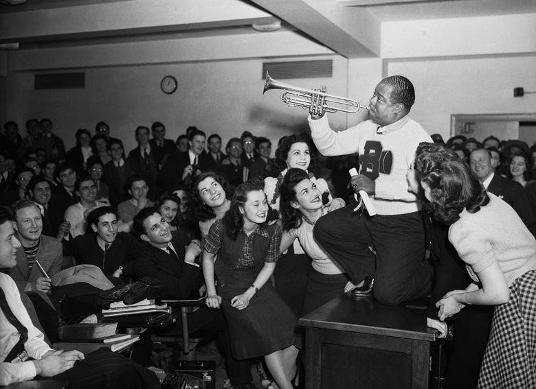 """FILE – In this March 12, 1941, file photo, Louis Armstrong, wearing a Brooklyn College sweater, performs on the campus in New York as the school honored him with the degree """"Doctor of Swing."""" Armstrong, Placido Domingo, Yo-Yo Ma, Audra McDonald, Leontyne Price and Harold Prince are this year's selections for the Performing Arts Hall of Fame at Lincoln Center. Jed Bernstein, president of Lincoln Center for the Performing Arts, made the announcement Thursday, Feb. 11, 2016. The honorees will be inducted June 20 during a ceremony at Lincoln Center's Alice Tully Hall.   (AP Photo/File)"""