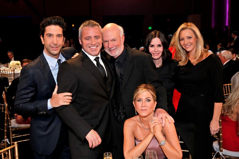 """In this image released by NBC, director James Burrows, standing center, poses with the cast of """"Friends,"""" from left,  David Schwimmer, Matt LeBlanc, Jennifer Aniston, seated, Courteney Cox and Lisa Kudrow during the taping of """"Must See TV: An All-Star Tribute to James Burrows,"""" airing Sunday at 9 p.m. EST on NBC.  (Chris Haston/NBC via AP)"""