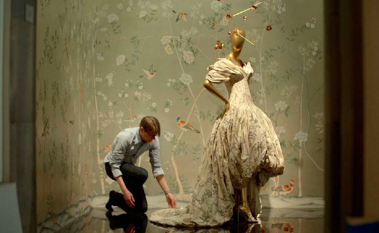 """This image released by Magnolia Pictures shows Andrew Bolton adjusting a dress on display in a scene from Andrew Rossi's documentary, """"The First Monday in May,"""" about the Metropolitan Museum of Art's costume exhibition on Chinese-inspired Western fashions. The film will open the 15th Tribeca Film Festival, running from April 13-24. (Magnolia Pictures via AP)"""