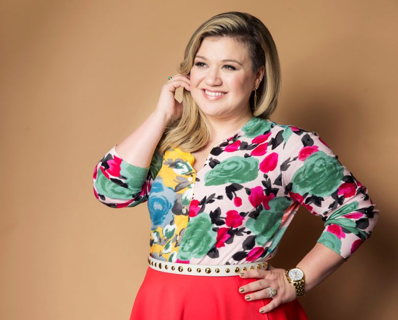 """FILE – In this March 4, 2015 file photo, American singer and songwriter Kelly Clarkson poses for a portrait to promote her album """"Piece by Piece"""" in New York. Clarkson has written a new song and a bedtime story for kids. """"River Rose and the Magical Lullaby,"""" will be released in October by HarperCollins Children's Books. (Photo by Victoria Will/Invision/AP, File)"""