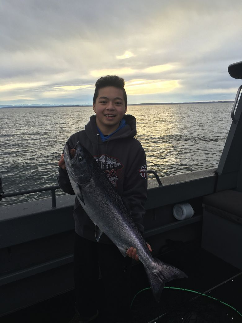Tegan Yuasa of Mercer Island holds a 13 pound hatchery chinook he caught on McArthur Bank near San Juan Island on Wednesday, Feb. 17, 2016. (Mark Yuasa/The Seattle Times)