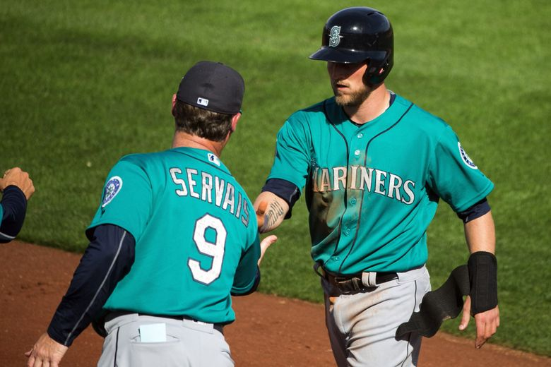 Infielder Shawn O'Malley gets a handshake from Manager Scott Servais after scoring on a two-run double by Luis Sardiñas in the top of the sixth as the Seattle Mariners play the San Diego Padres.  (Bettina Hansen / The Seattle Times)