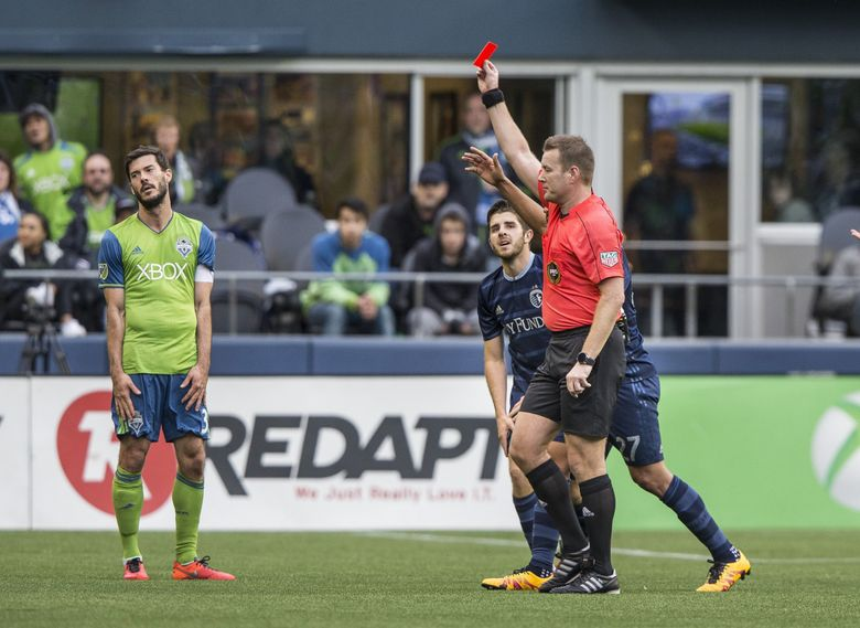 Sounders captain Brad Evans, left, reacts to the red card issued to teammate Oniel Fisher by referee Alan Kelly in the first half. (Dean Rutz / The Seattle Times)
