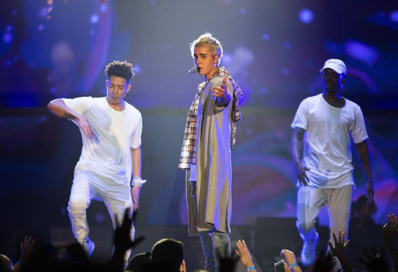 Justin Bieber points at the audience as he sings during at KeyArena on Wednesday. (Lindsey Wasson / The Seattle Times)