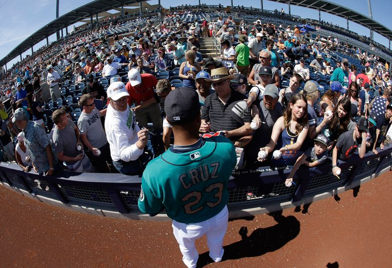 Mariners slugger Nelson Cruz remains hugely popular with fans as evidenced by those waiting for him to sign autographs Sunday against the Cincinnati Reds in Arizona despite going 0 for 13 to start spring training. (Darron Cummings/AP)