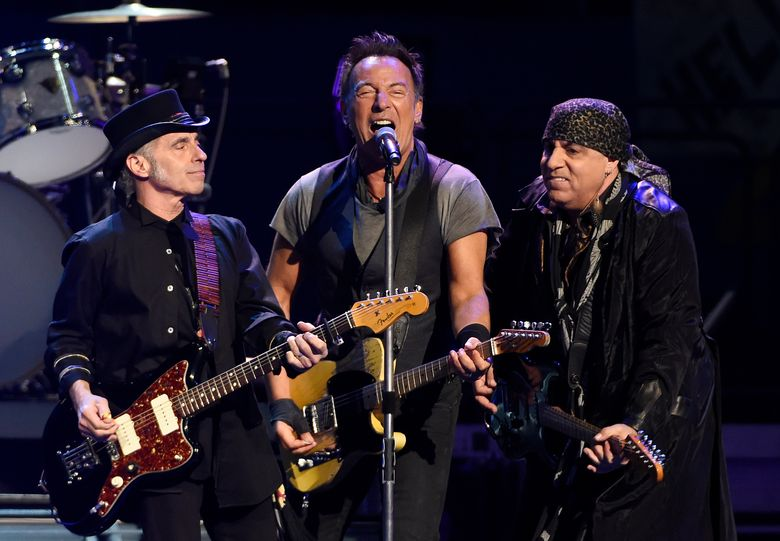 """FILE – In this Tuesday, March 15, 2016 file photo, Bruce Springsteen, center, performs with Nils Lofgren, left, and Steven Van Zandt of the E Street Band during their concert at the Los Angeles Sports Arena in Los Angeles. Fourth-grader Xabi Glovsky and his father, Scott, attended the sold-out show, and they caught Springsteen's eye with a homemade sign that said: """"Bruce, I will be late to school tomorrow. Please sign my note."""" After the show, Springsteen invited the pair backstage and he scribbled a note for the Claremont boy's teacher. The note said: """"Dear Ms. Jackson, Xabi has been out very late rocking & rolling. Please excuse him if he is tardy."""" (Photo by Chris Pizzello/Invision/AP)"""