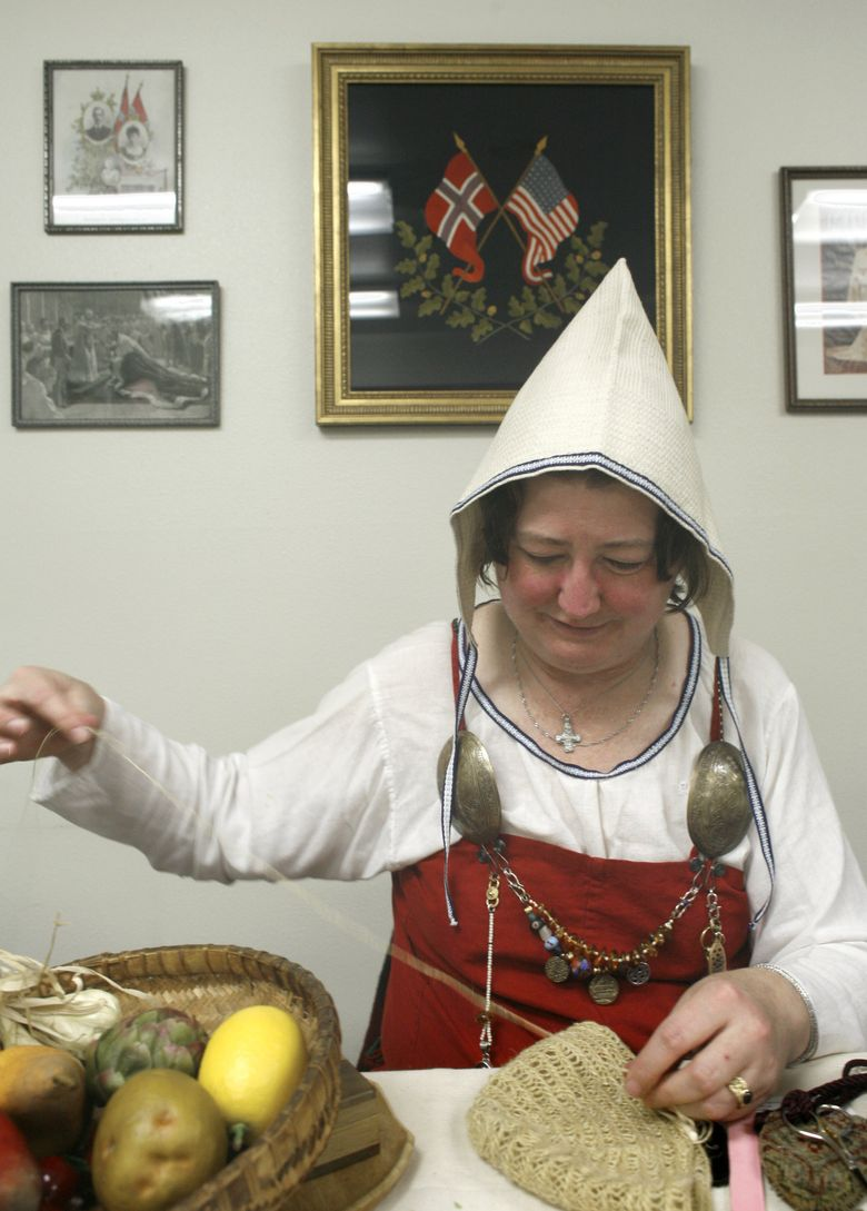 """Wearing replica Viking clothing, Pat Reed, of Bothell, does """"nalbinding""""at a previous Norwegian heritage day. (Betty Udesen/The Seattle Times)"""