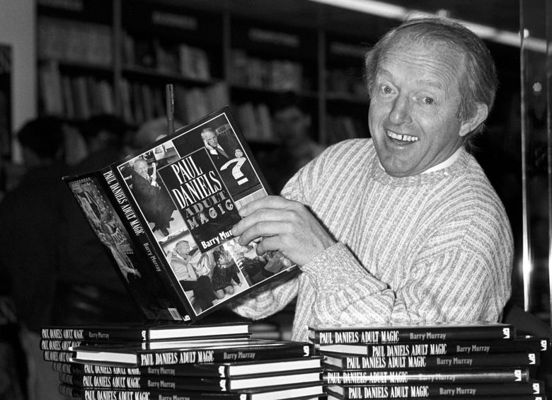FILE – This is a Dec. 2, 1989 file photo of  British magician Paul Daniels as he holds with a copy of his book 'Adult Magic' at Whiteleys book shop in London. Daniels, best known for The Paul Daniels Magic Show that regularly attracted 15 million TV viewers in Britain and was sold to 43 countries, has died after suffering from an inoperable brain tumor. He was 77.  His publicist, Bex Colwell, said, in a statement that Daniels died Thursday March 17, 2016, at his home in Berkshire, 60 miles (95 kms) west of London with his wife by his side.  (PA/File via AP) UNITED KINGDOM OUT