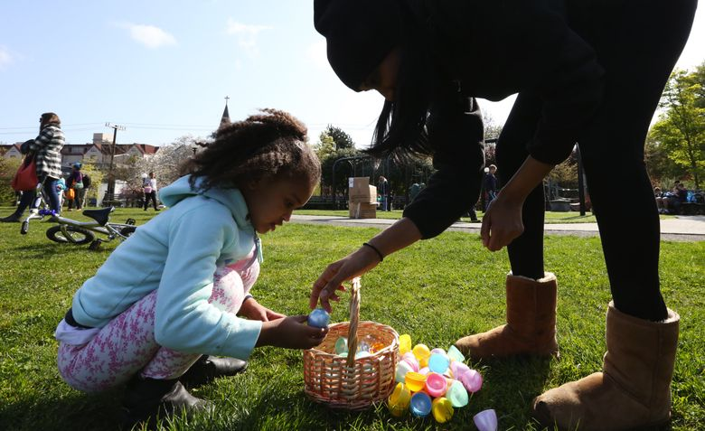 Rahel Adane helps her daughter, Leah, sort through the eggs gathered at last year's hunt at Cal Anderson Park. Many Seattle community centers and local groups will hold Easter egg hunts on Saturday, March 26.  (Alan Berner/The Seattle Times)