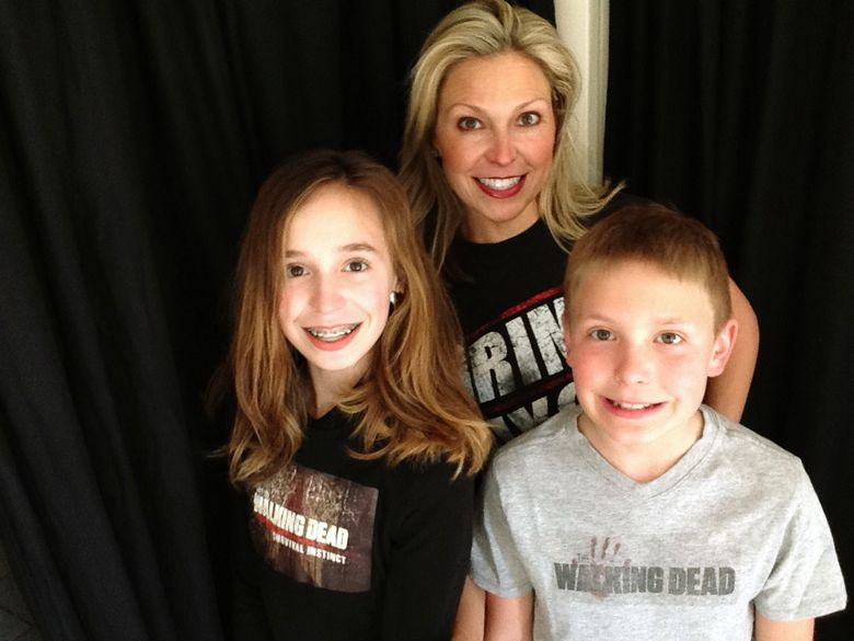 """This March 29, 2016 photo released by Ericka Calcagno, center, shows her with her daughter Gina Binder, 12, left, and son Jean-Luc Binder, 9, wearing T-shirts from, """"The Walking Dead,"""" at their home in Farmington Hills, Mich. Calcagno says her husband first introduced her to the series and her kids were intrigued by their conversations about it. And now they all watch the popular zombie show as a family.  (Ericka Calcagno via AP)"""