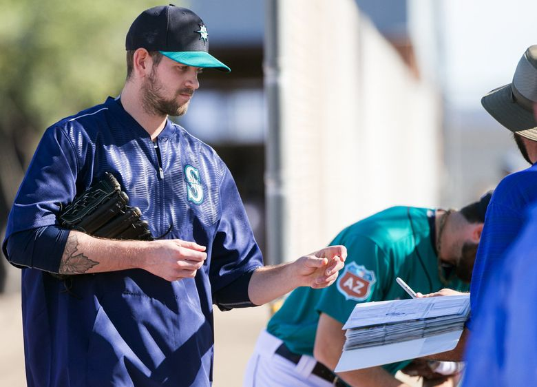 Pitcher James Paxton signs an autograph for a fan as pitchers and catchers work out at Seattle Mariners spring training in Peoria, Arizona, Wednesday February 24, 2016.