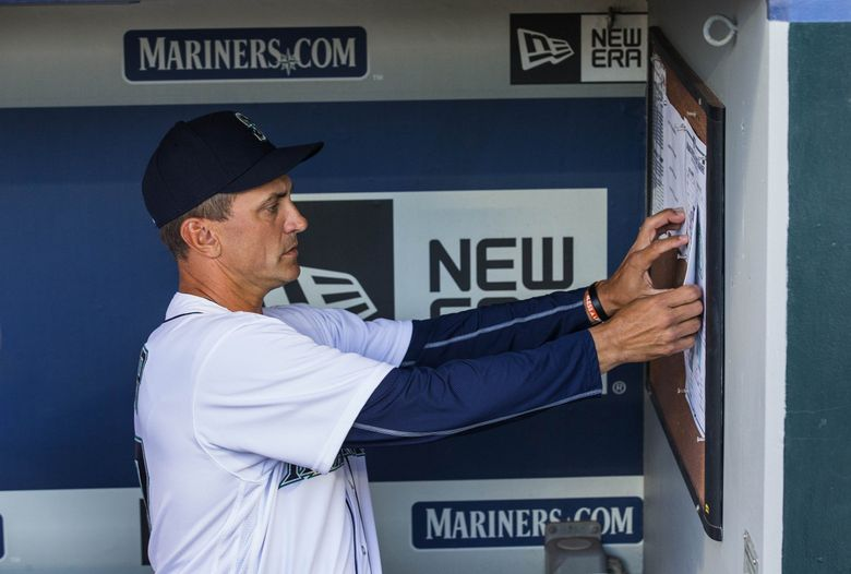 Bench coach Tim Bogar puts the starting lineup for Seattle on the dugout wall Saturday.  The Seattle Mariners and Oakland A's played the second game of a three game set Saturday at Safeco Field in Seattle.  (Dean Rutz / The Seattle Times)