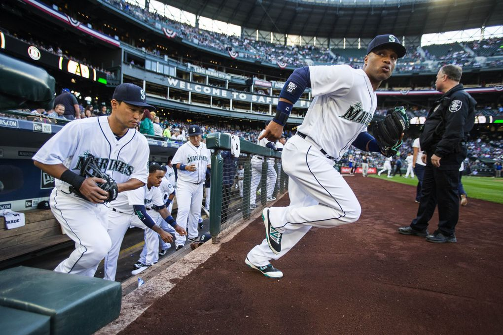 Robinson Cano leads the Mariners onto the field to play Oakland on April 9 in Seattle. (Dean Rutz / The Seattle Times)