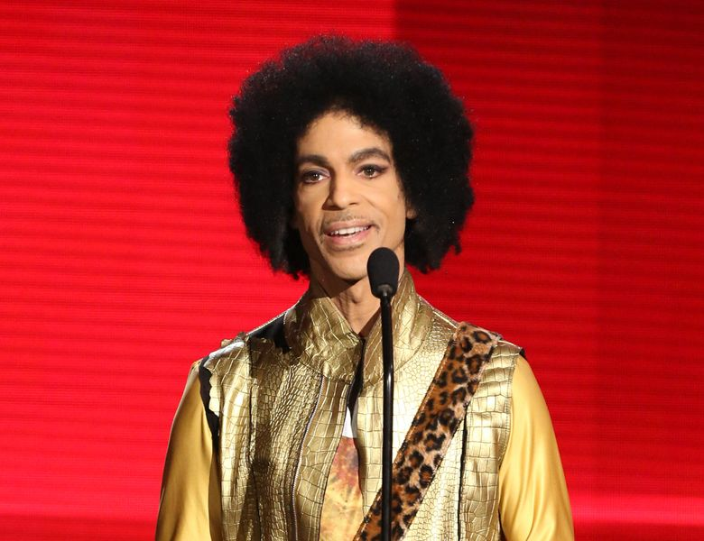 """FILE – In this Nov. 22, 2015 file photo, Prince presents the award for favorite album – soul/R&B at the American Music Awards in Los Angeles. Prince, widely acclaimed as one of the most inventive and influential musicians of his era with hits including """"Little Red Corvette,"""" """"Let's Go Crazy"""" and """"When Doves Cry,"""" was found dead at his home on Thursday, April 21, 2016, in suburban Minneapolis, according to his publicist. He was 57. (Photo by Matt Sayles/Invision/AP, File)"""