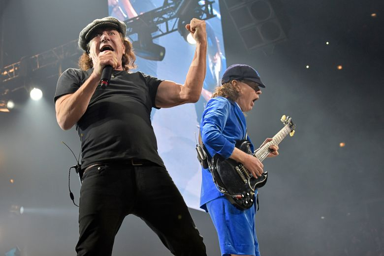"""FILE – In this Feb. 17, 2016 file photo, Brian Johnson, left, and Angus Young perform with AC/DC on the Rock or Bust Tour in Chicago.  Johnson says he's not retiring from music after doctors told him that he risks substantial hearing loss if he continues to perform in large arenas and stadiums. Johnson said in a statement released through his publicist on Tuesday, April 19, that he intends to continue to record in studios and will continue treatment to improve his hearing. The """"Back in Black"""" singer will be replaced by Guns N' Roses singer Axl Rose for the Rock or Bust World Tour beginning May 7 in Lisbon. (Photo by Rob Grabowski/Invision/AP, File)"""