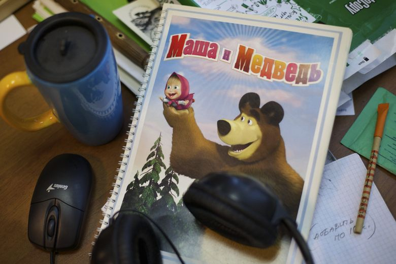 """A notebook with the characters of cartoon TV series """"Masha and the Bear"""" lays on the desk at the Animaccord production company's office in Moscow, Russia. (Ivan Sekretarev/The Associated Press)"""