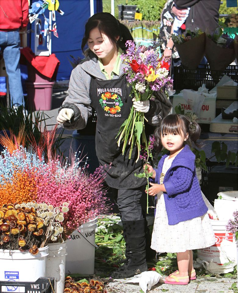 Moua Vang, with her daughter Lotus Chang, does brisk business at the Burien Farmers Marketin 2012. This year the market opens Thursday, May 5. (Jim Bates/The Seattle Times)