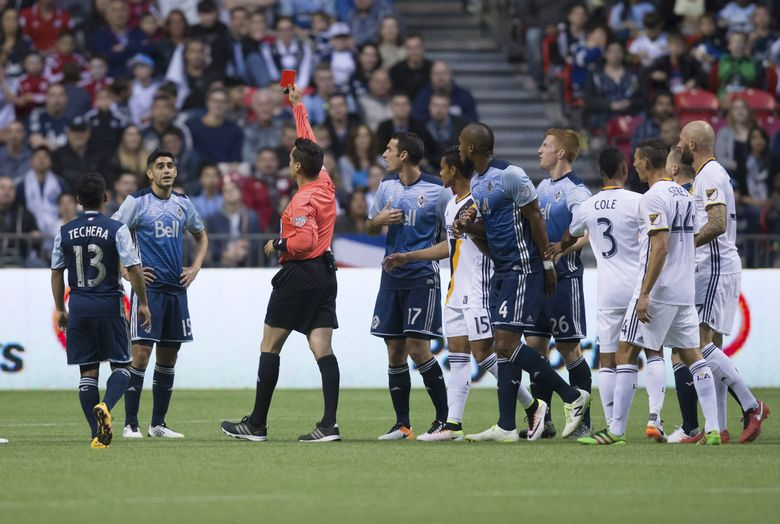 Vancouver Whitecaps' Matias Laba, second from left, receives a red card from referee Jair Marrufo during the first half of an MLS soccer game against the Los Angeles Galaxy on Saturday, April 2, 2016, in Vancouver, British Columbia. (Darryl Dyck/The Canadian Press via AP)