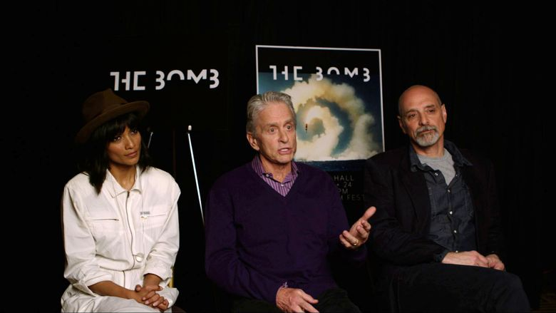 """In this image made from video, Michael Douglas, center, sits with filmmakers Smriti Keshari, left, and Eric Schlosser, Saturday, April 23, 2016, in New York. Their groundbreaking multimedia installation on the threat of nuclear war, """"The Bomb,"""" will close the Tribeca Film Festival. Douglas wore purple to honor the late music icon, Prince. (AP Photo)"""