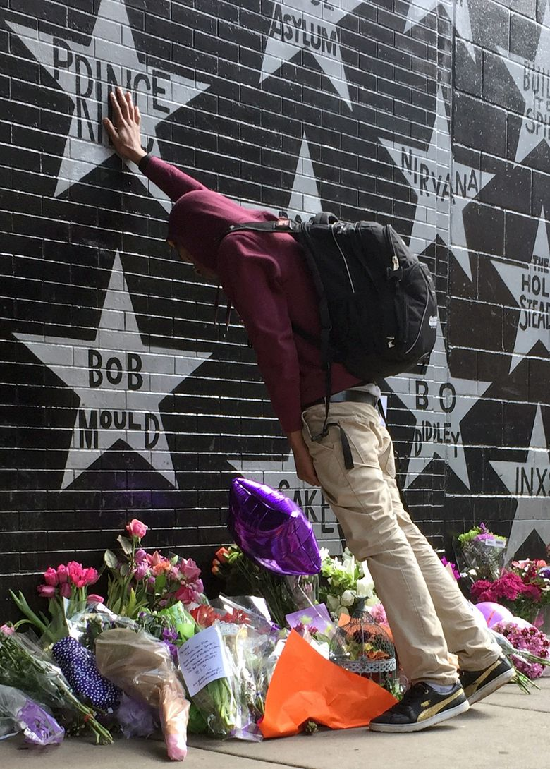 """Terrance May, a musician who goes by the name May Millions, takes a moment at a growing memorial outside First Avenue, a Minneapolis club where Prince filmed a large portion of his classic movie """"Purple Rain"""" and recorded several songs on the accompanying album in Minneapolis, Thursday, April 21, 2016. Prince one of the most inventive and influential musicians of modern times with hits including """"Little Red Corvette,"""" """"Let's Go Crazy"""" and """"When Doves Cry,"""" was found dead at his home on Thursday in suburban Minneapolis. He was 57. (AP Photo/Kevin Burbach)"""
