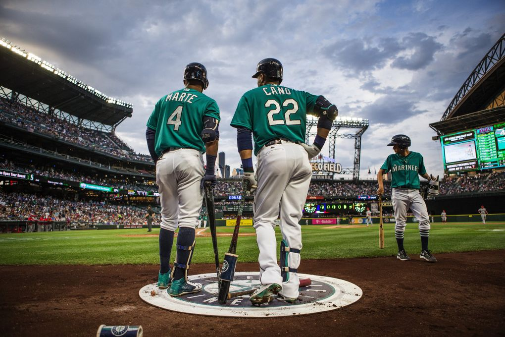 Ketel Marte and Robinson Cano talk in the warmup circle before their at-bats against the Angels on May 13 at Safeco Field. (Dean Rutz / The Seattle Times)