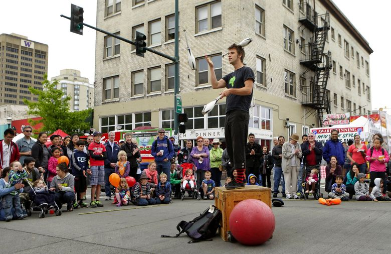 """""""One Fine Fool,"""" Jules McEvoy, 30, a performer from Bellingham, dazzles a crowd with his juggling and theatrical skills at the 44th annual University District Street Fair Sunday May 19, 2013.  (Bettina Hansen / The Seattle Times)"""