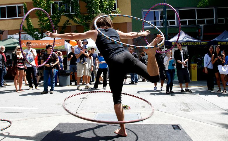 Jon Coyne, aka Hoopsmiles, performs at a past University District Street Fair. This year's fair runs Saturday and Sunday, May 21-22.  (ALAN BERNER/The Seattle Times)