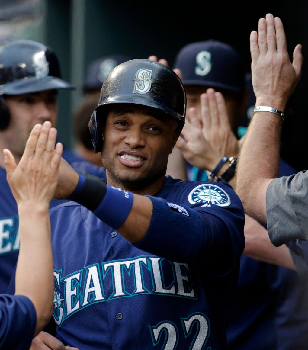 Mariners' Robinson Cano high-fives teammates in the dugout after scoring on a single by Nelson Cruz on May 17 in Baltimore. (Patrick Semansky / AP)