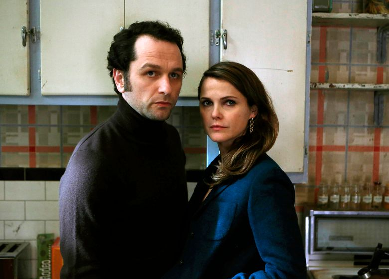 """In this image released by FX, Matthew Rhys, left, and Keri Russell appear in a scene from """"The Americans."""" The show will conclude its series run on FX with two more seasons, the network announced Wednesday, May 25, 2016. A 13-episode fifth season will air in 2017, followed by a 10-episode sixth and final season in 2018, FX said.  (Craig Blankenhorn/FX via AP)"""