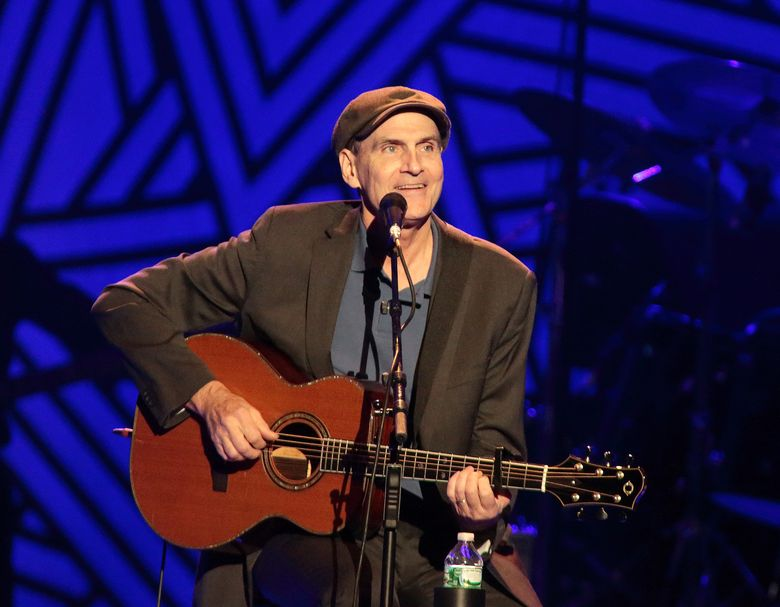 """FILE – In this July 9, 2015 file photo, singer-songwriter James Taylor performs in concert at the Giant Center in Hershey, Pa. Taylor is using his music to help people evacuated from a huge wildfire in Canada. The """"Carolina in My Mind"""" singer has made two Alberta concerts next month into benefits. He says proceeds from tickets to his shows in Calgary on June 7, 2016, and Edmonton on June 8 will be donated to the Canadian Red Cross. (Photo by Owen Sweeney/Invision/AP, File)"""