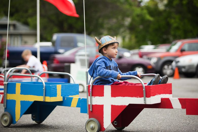 """Edward Pace takes a ride in the """"Bjorn Deere"""" outside the Nordic Heritage Museum during the 2015 Syttende Mai 17th of May Festival in Ballard. This year's event is on Tuesday. (Lindsey Wasson / The Seattle Times)"""