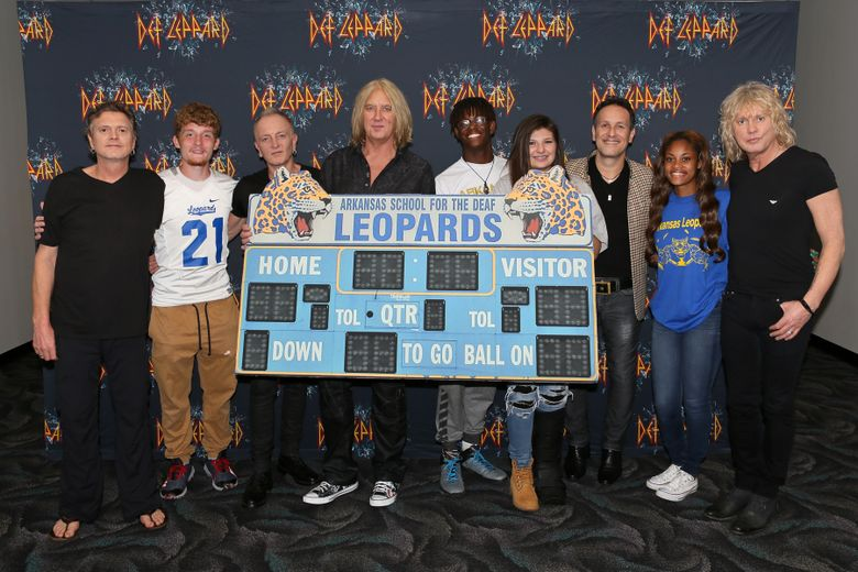 """CORRECTS DATE TO MAY 11 – In this May 11, 2016 photo provided by Nelson Chenault, from left, Def Leppard drummer Rick Allen, student Stephen Cathcart, guitarist Phil Collen, lead singer Joe Elliott, student Henry James, student Alex Gossett, guitarist Vivian Campbell, student Jewel Brandon and bassist Rick Savage pose with a replica of the scoreboard from the Arkansas School for the Deaf, before a concert in North Little Rock, Ark. The British rockers behind a string of hits in the 1980s and '90s including """"Pour Some Sugar on Me"""" and """"Photograph"""" met with students whose team's name is the Leopards. (Nelson Chenault via AP)"""