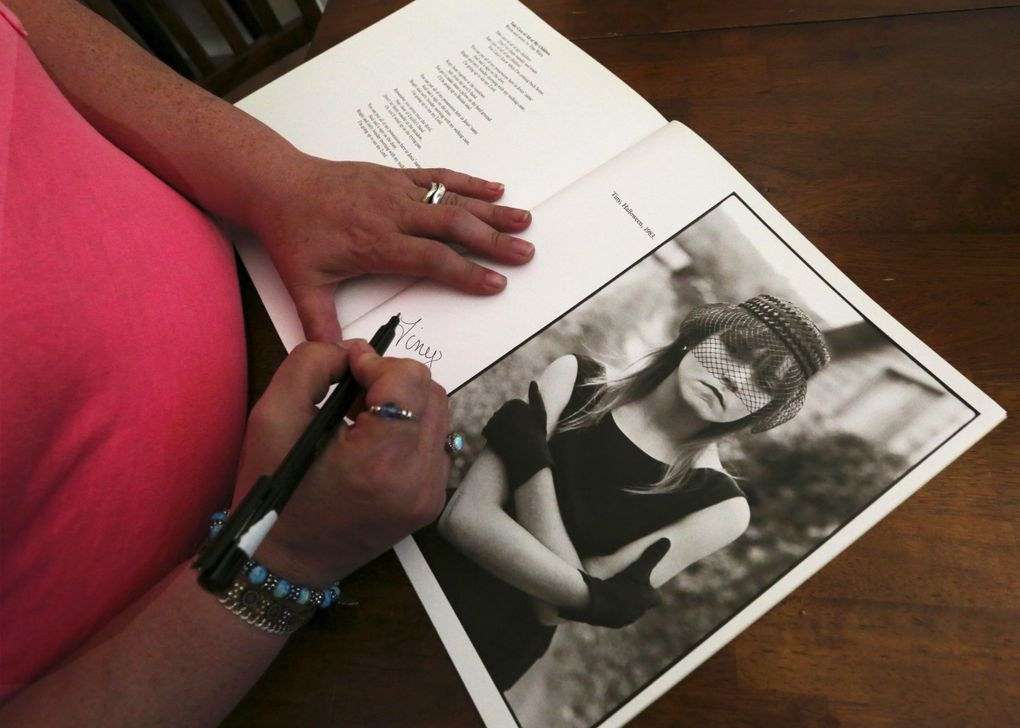 """Erin """"Tiny"""" Blackwell signs a copy of photographer Mary Ellen Mark's book """"Streetwise"""" next to a photograph of herself at age 13 in 1983.  (Alan Berner/The Seattle Times)"""