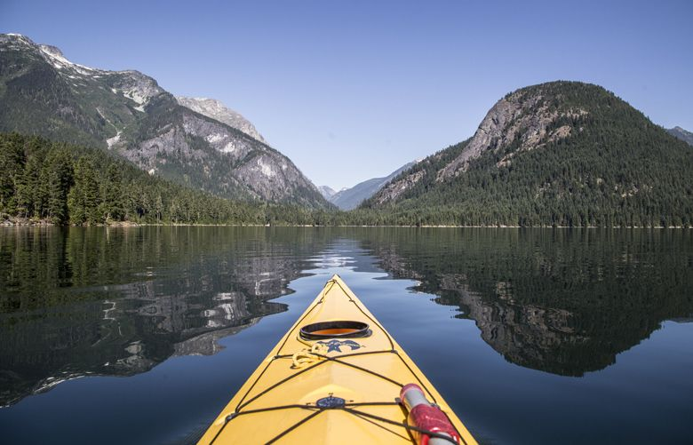 Kayaking on Ross Lake between the shadows of an unidentified peak at left and Pumpkin Mountain at right. In the saddle between is the Big Beaver Creek trail in the North Cascades National Park.