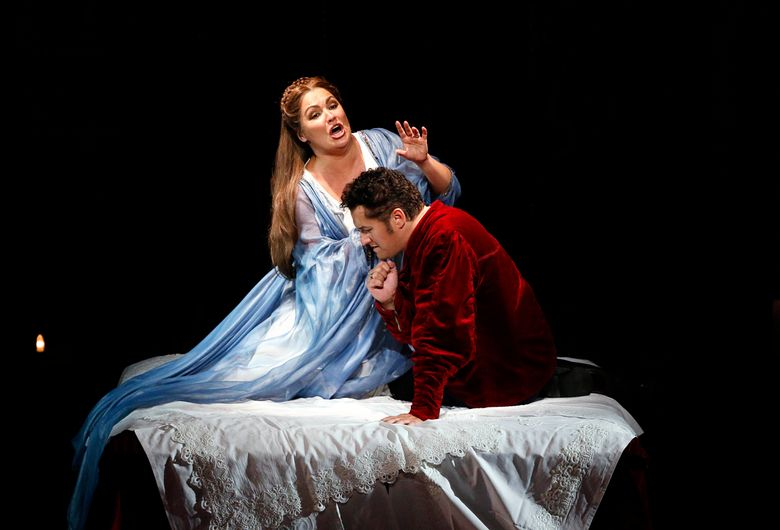 """In this undated image released by the Semperoper Dresden, Soprano Anna Netrebko, left, and tenor Piotr Beczala perform in Wagner's opera """"Lohengrin"""" at the Semperoper Dresden in Germany. Their debuts in """"Lohengrin"""" as Elsa, the maiden in distress, and her heroic knight have drawn raves from critics and standing ovations from audiences, who snapped up every ticket for the four-performance run at the Semperoper Dresden ending Sunday, May 29. (Daniel Koch/Semperoper Dresden via AP)"""