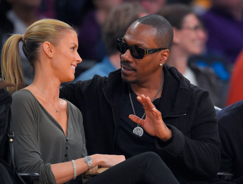 FILE – In this April 12, 2015, file photo, actor Eddie Murphy talks with his girlfriend Paige Butcher during an NBA basketball game between the Los Angeles Lakers and the Dallas Mavericks. Murphy and Butcher welcomed their first child together on May 3, 2016.  (AP Photo/Mark J. Terrill, File)