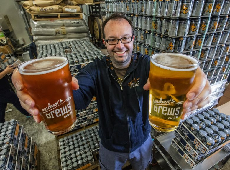 Reuben's Brews brewmaster Adam Robbings hoists a glass of Crikey IPA in his right hand and a Pilsner in his left. (Steve Ringman / The Seattle Times)