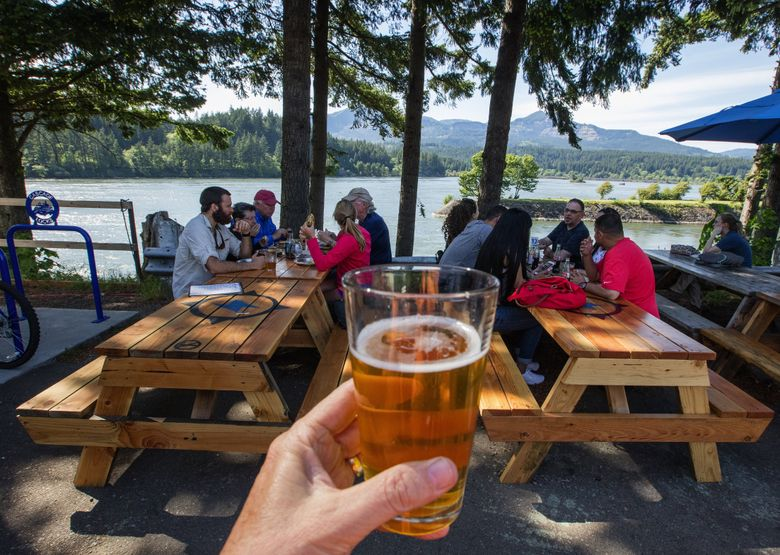 Diners and beer drinkers enjoy riverside tables at Thunder Island Brewing in Cascade Locks, Ore., near the route of the Historic Columbia River Highway.  (Steve Ringman/The Seattle Times)