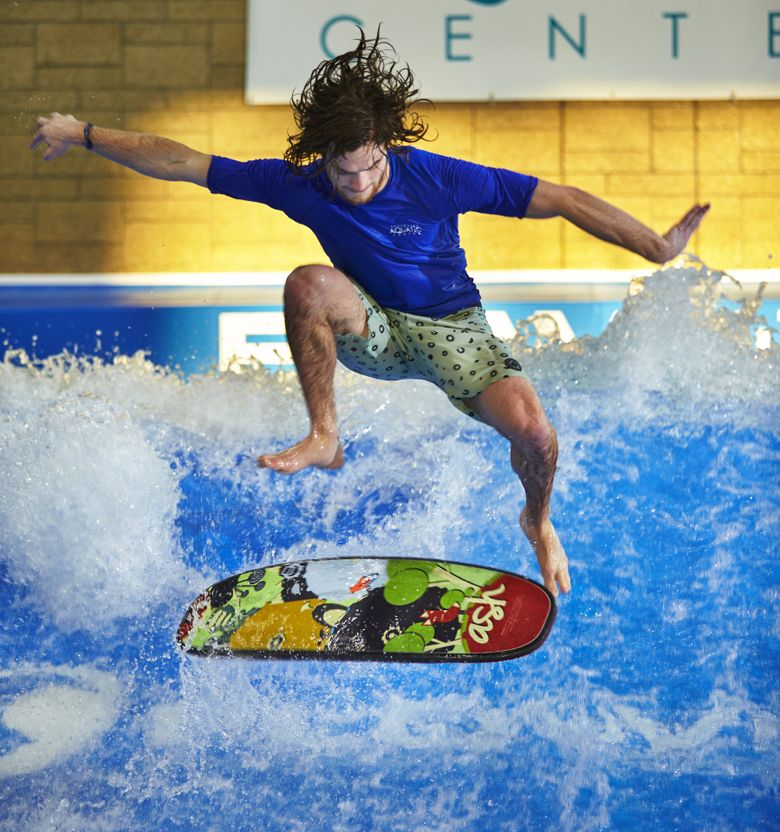 FlowRider instructor Scott Callens takes a spin for fun after teaching a class at the Snohomish Aquatic Center. (Benjamin Benschneider / The Seattle Times)