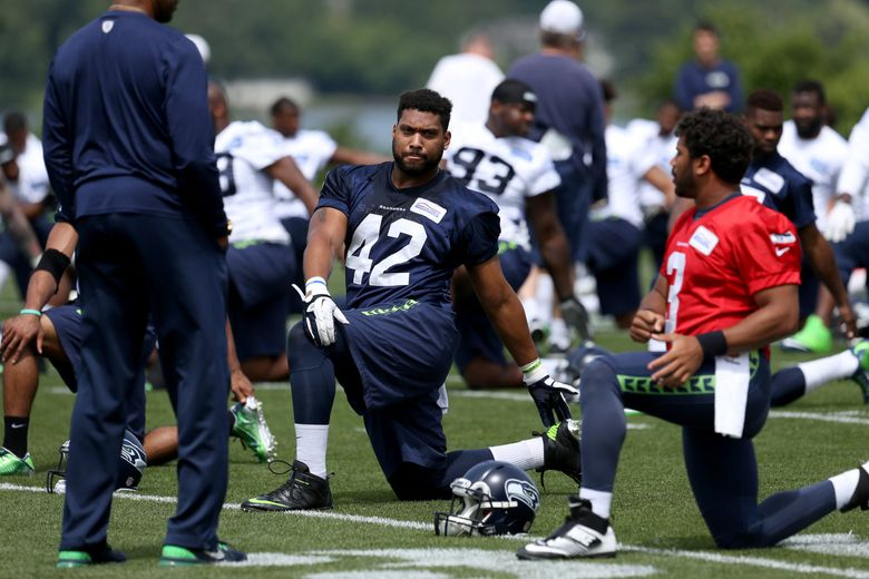 Seattle Seahawks tight end Brandon Cottom (42) stretches alongside quarterback Russell Wilson (3) during organized team activities on Wednesday. (Johnny Andrews / The Seattle Times)