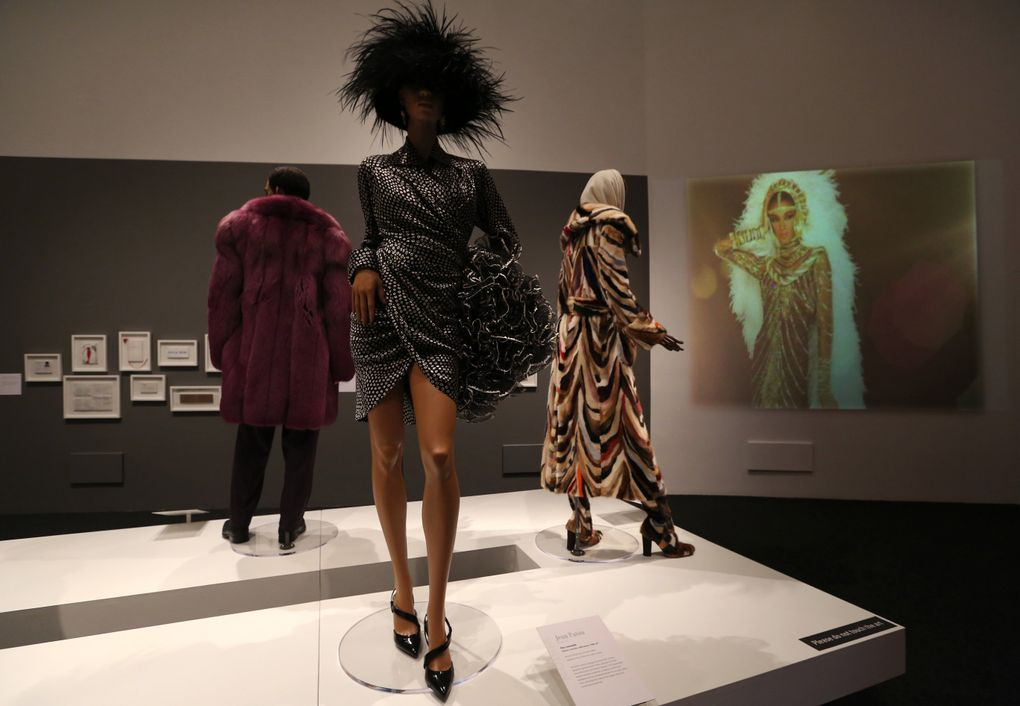 """A 1980s day dress and muff from Jean Patou, flanked by a bold purple coat and suit by Giorgio Casani, left, and a coat with matching boots from Laura Biagiotti, part of """"Inspiring Beauty: 50 Years of Ebony Fashion Fair,"""" a touring exhibit from the Chicago History Museum, at BAM.  (Alan Berner/The Seattle Times)"""