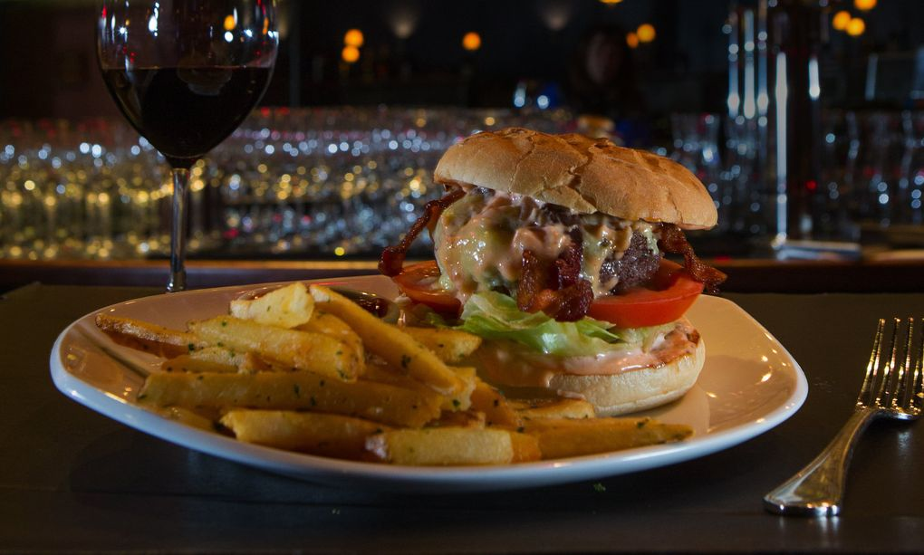 El Gaucho's 410 Burger features a ½-pound patty of Niman Ranch Angus beef topped with English Coastal cheddar, bacon and Thousand Island dressing served on a brioche bun. It's served with duck-fat fries, and it's as big, rich and classic as the steakhouse itself.  (Ellen M. Banner/The Seattle Times)