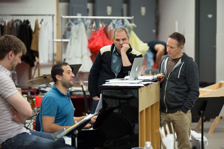 """5th Avenue Theatre artistic director David Armstrong, standing at center, and playwright Jon Marans, right, work on """"Paint Your Wagon"""" at the 5th's rehearsal hall."""
