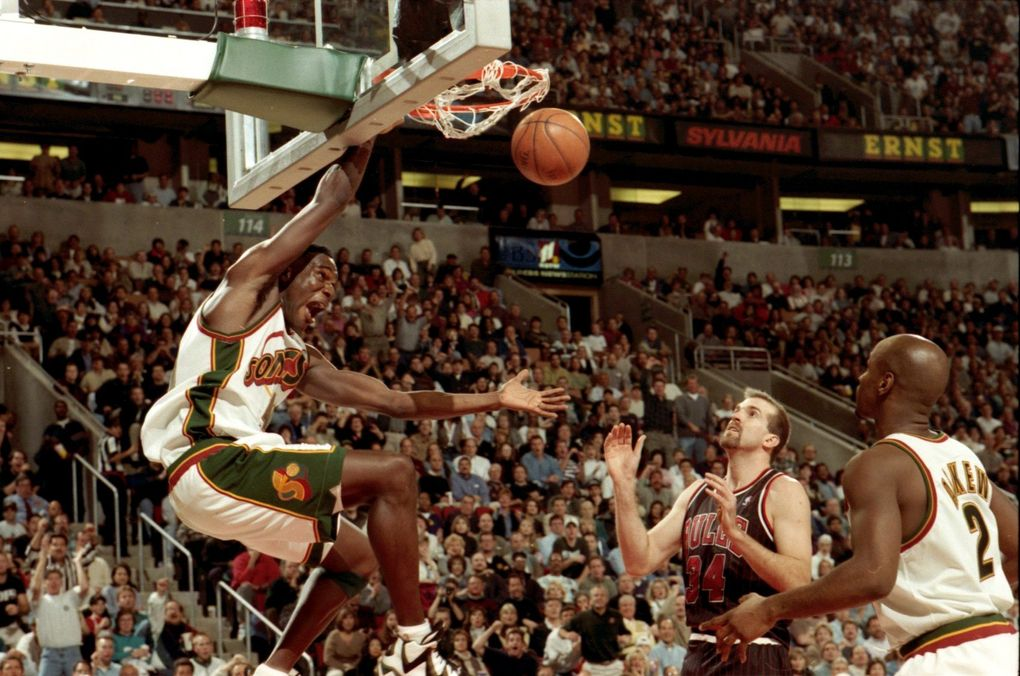 Sonics forward Shawn Kemp dunks after snatching a pass above the rim from Gary Payton in a game against the Chicago Bulls. (Mark Harrison/The Seattle Times)