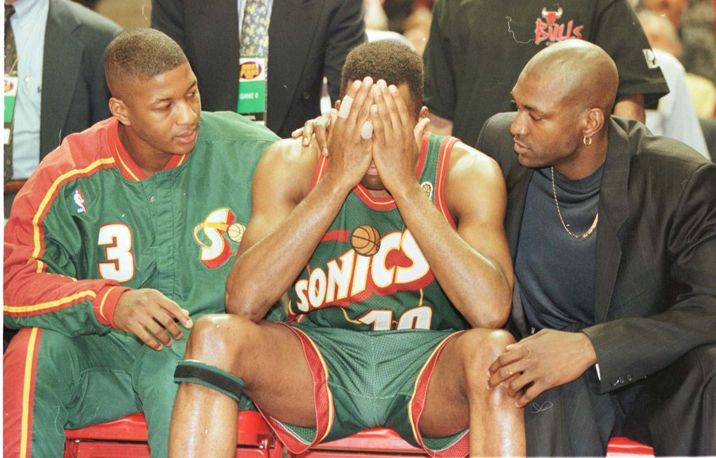 Eric Snow, left, and Sherrell Ford, right, comfort Nate McMillan as he weeps on the bench late in Game 6 of the 1996 NBA Finals. (Seattle Times file)