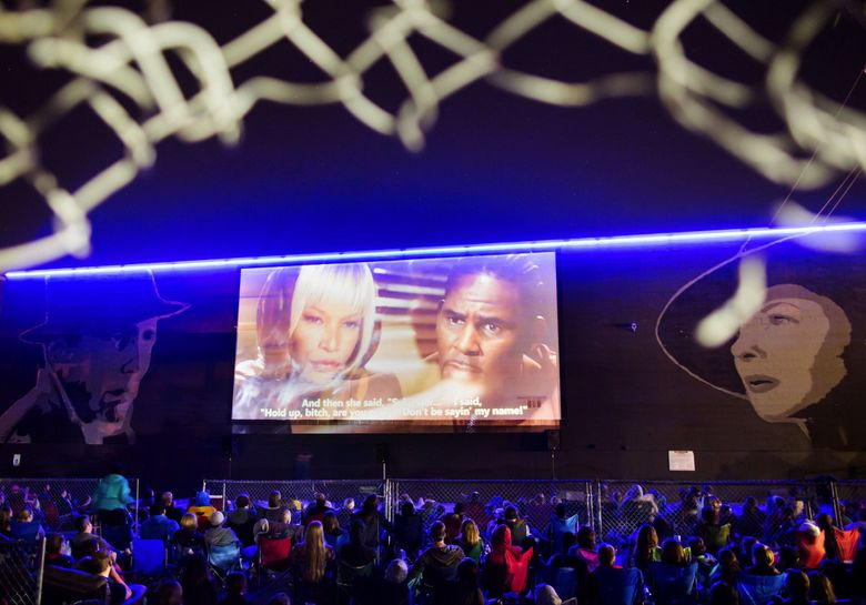 """A few hundred people armed with movie props participate at the showing of R. Kelly's """"Trapped In A Closet"""" sing along event at Fremont Outdoor Movies in Seattle, on Saturday, Aug. 3, 2013.  (Marcus Yam / The Seattle Times)"""