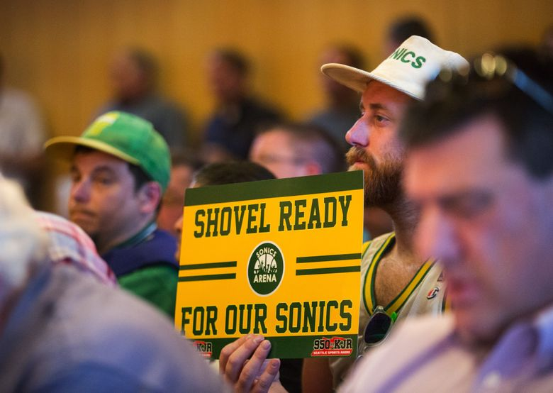 Sonics fan Andrew Wergeland-Rammage holds a sign saying as he listens to Seattle City Council proceedings in May 2016. (Lindsey Wasson / The Seattle Times)