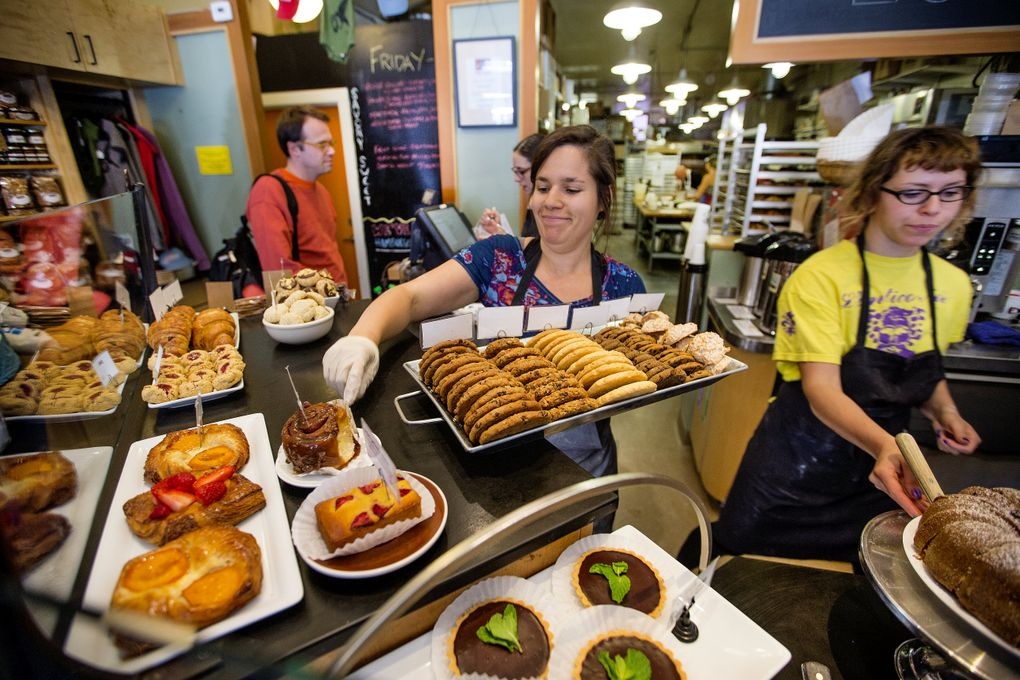 Leah Champagne puts out a tray of freshly baked cookies at Seattle's Columbia City Bakery. The bakery, at 4865 Rainier Ave. S., makes a good side trip for cyclists riding Lake Washington Boulevard on Bicycle Sundays this summer. (Mike Siegel/The Seattle Times)