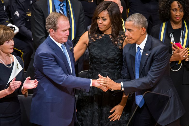 Former President George W. Bush shakes hands with President Barack Obama during an interfaith memorial service for the fallen police officers and members of the Dallas community, Tuesday, July 12, 2016, at the Morton H. Meyerson Symphony Center in Dallas. Former first lady Laura Bush is a left and first lady Michelle Obama is at center. (Smiley N. Pool/The Dallas Morning News via AP)